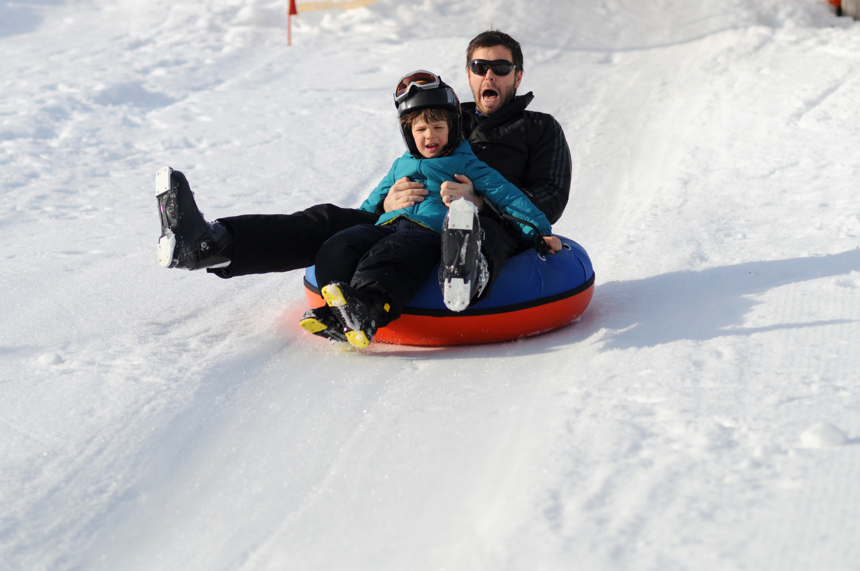 Father and son sliding down on snow tubes